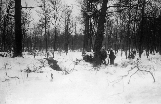 "Men of the 106th Division take up positions in the snowy woods near St. Vith, December 1944. The ""Golden Lion"" Division suffered heavy casualties during the battle, losing over 6,600 men taken prisoner."