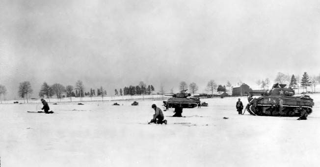 During heavy fighting against German forces in the vicinity of Bastogne, armored infantrymen of the 6th Armored Division advance cautiously across a snow-covered meadow. Sherman tanks are visible in support of the advance.