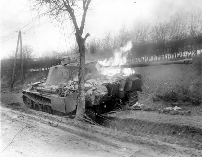 A German PzKpfw. V Panther medium tank, its long-barreled 75mm main gun jutting from the tur- ret, blazes after being knocked out in combat in the vicinity of Bastogne, the vital Belgian crossroads town that played a pivotal role in the Battle of the Bulge.