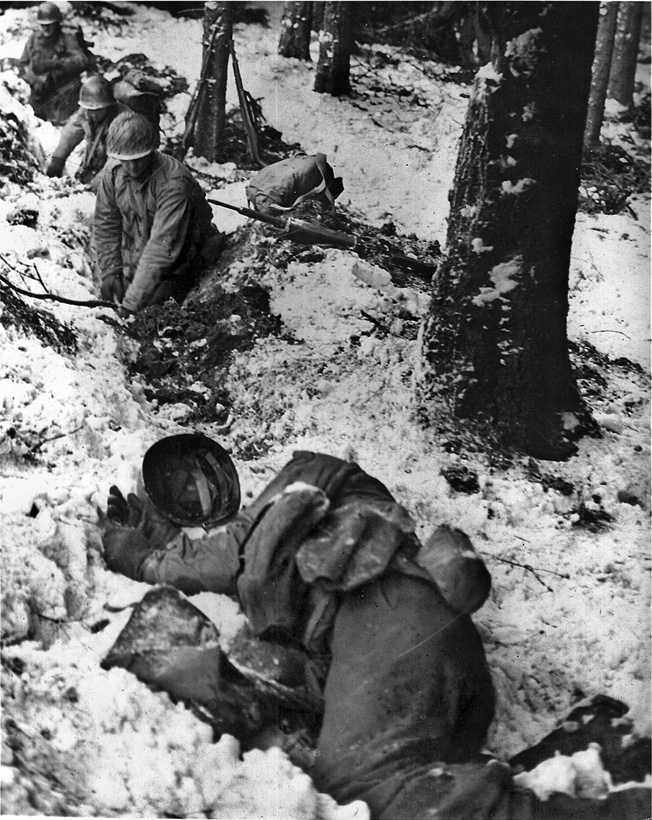 An unidentified American soldier lies dead as members of his unit hastily dig foxholes in a roadside ditch during the German breakthrough in the Ardennes, December 1944.