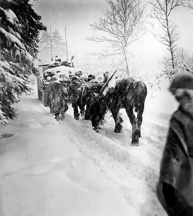 "Troops from H Company, 82nd Airborne Division, advance in a snowstorm behind a tank. The packhorse, which was not U.S. government issue, was likely ""borrowed"" from a local farm."