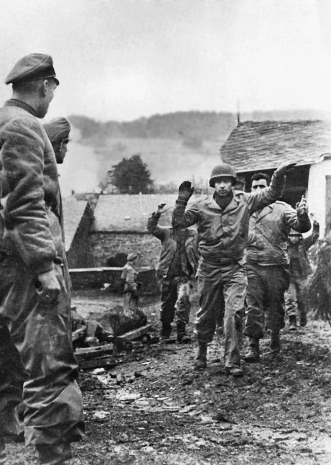With their hands up, American soldiers surrender to men of the 1st SS Panzer Division in a Belgian village.