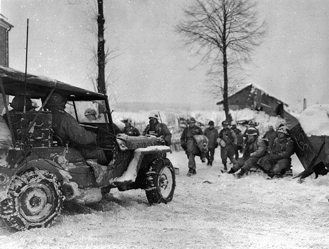 Men of the 505th Parachute Regiment, 101st Airborne, move into a town during the Battle of the Bulge.