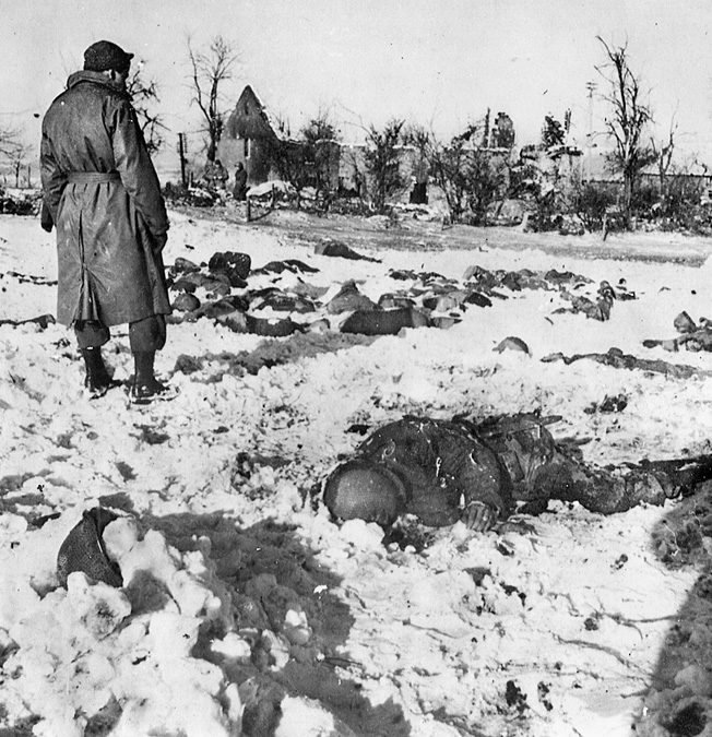 A GI surveys the snowy field littered with dead Americans massacred at Baugnez, near Malmédy.
