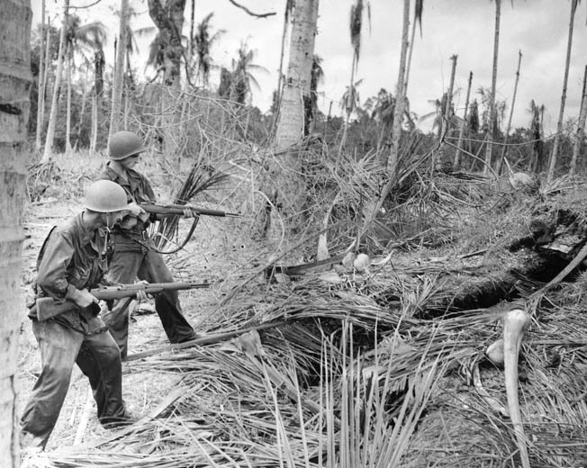 Two 32nd Division soldiers clear a well-concealed Japanese bunker near Buna Mission, late 1942. During the campaign, both sides suffered from the harsh climate, disease, and terrain.