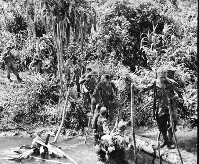Men of the 128th Infantry, 32nd Division, the Wisconsin and Michigan National Guard, cross a makeshift bridge on their way to Embogu, November 5, 1942.