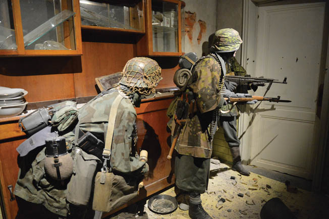 One of the realistic dioramas depicts three SS soldiers on the alert in a Belgium home.