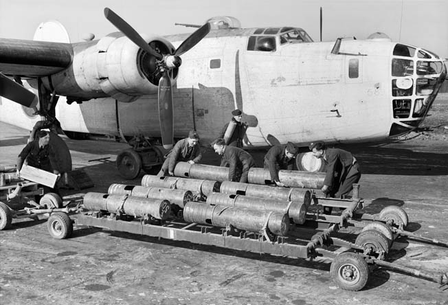 Royal Air Force armorers load 250-pound Mark VIII depth charges aboard a Consolidated Liberator Mark VA bomber of RAF Coastal Command. This aircraft is from No. 53 Squadron based at St. Eval.