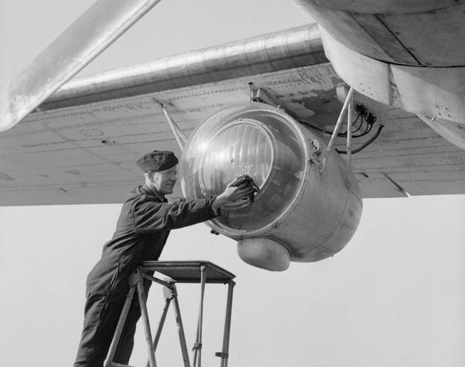 An excellent innovation deployed with sub-hunting aircraft that patrolled the Bay of Biscay, the Leigh Light was used to illuminate German U-boats on the surface and facilitate the speed of attacks. In this photo a Royal Air Force ground crewman cleans the plexiglass cover of a Leigh Light that has been installed under the wing of a Consolidated Liberator bomber.