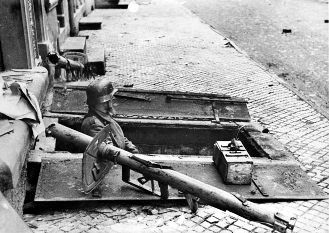 An antitank panzerschreck by his side, a German soldier peers from the doors of a cellar inside Aachen.
