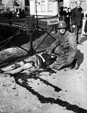 A lieutenant from Patton's Third Army with the mangled body of a German girl accidentally killed when an Me-109 attacked American troops in the town of Muhlhausen.