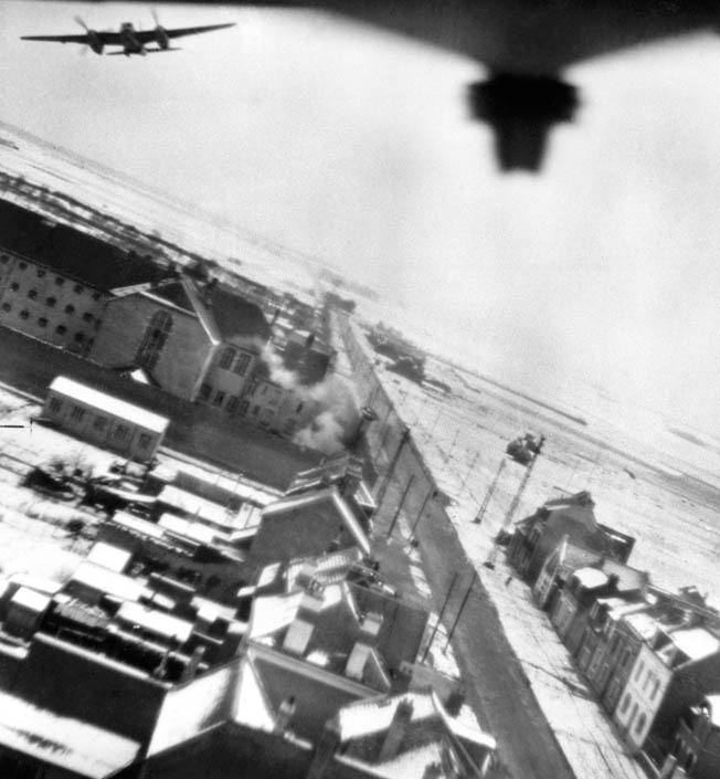 Mosquitos of No. 487 Squadron, Royal New Zealand Air Force, flying low over the Amiens prison as the first of 16 500-pound bombs explode. Over 250 prisoners—French Resistance and Allied intelligence officers—were able to escape.