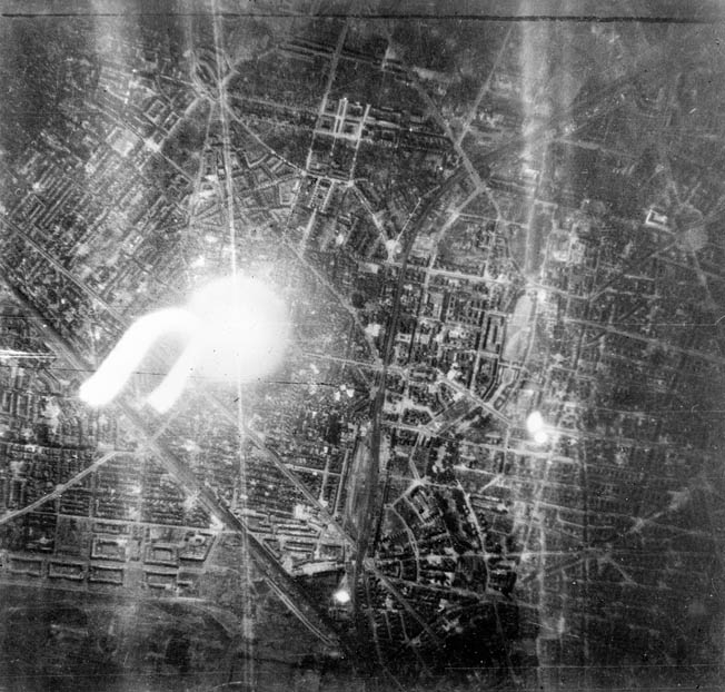 A target indicator, shown at left in this photo, illuminates the Schoneburg District of the Nazi  capital of Berlin during a raid by 27 De Havilland Mosquito bombers conducted in September 1944.