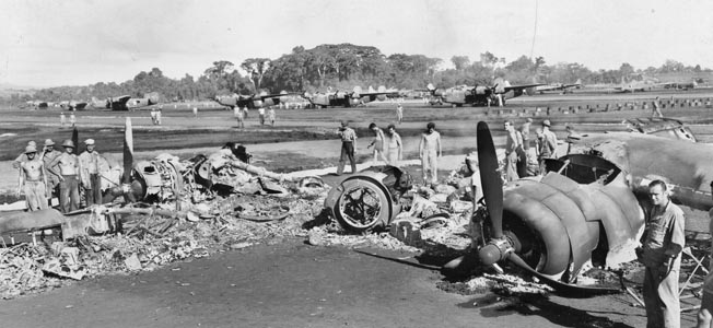 The wreckage of a Consolidated B-24 Liberator bomber lies burned on the runway at Henderson Field after a Japanese air raid.