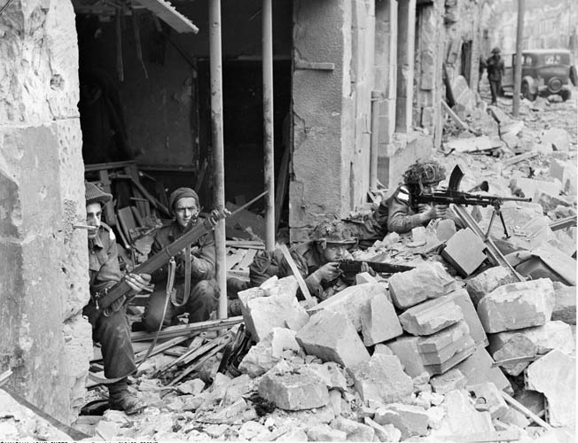 Fighting was intense in the towns and villages behind Juno Beach. Here, 3rd Canadian Infantry Division soldiers defend their position in a French town. Three of the soldiers are equipped with Lee Enfield Mk I rifles while the soldier at right is firing a Bren .303 Mk II machine gun.