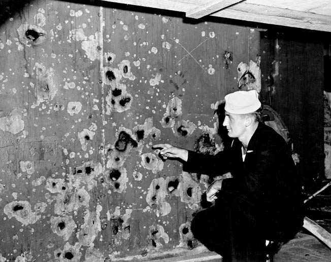 A sailor points to damage sustained by the cruiser USS Boise during the Battle of Cape Esperance. This shredded bulkhead was hit by fragments from a shell that exploded only 30 feet away. This photo was taken during repairs at the Philadelphia Navy Yard.