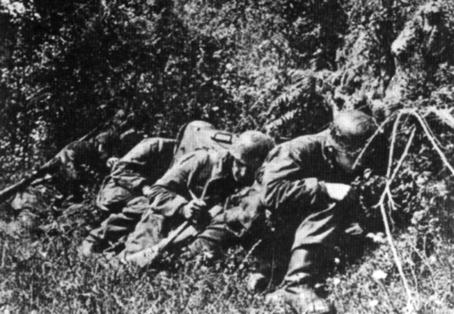 Using the protective bank of a Normandy hedgerow, members of FJR 6 take cover from an attack by an American fighter-bomber.