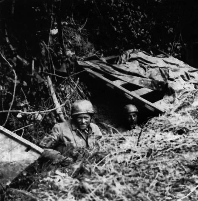 Paratroopers from Fallschirmjäger Regiment 6 use wood, tarpaulins, and foliage to camouflage their defensive position in Normandy.