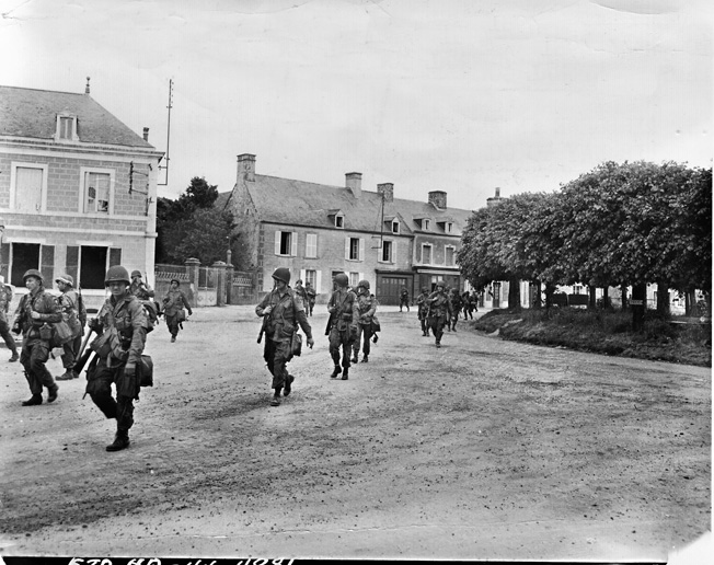 101st Airborne troops march through the town of Ste.-Marie-du-Mont that had once been a FJR 6 stronghold.