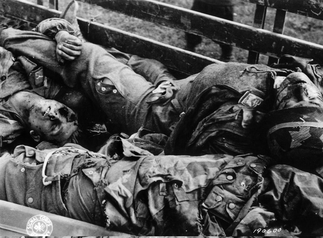 Three German soldiers lie dead in an American vehicle before being taken to a temporary cemetery and buried.