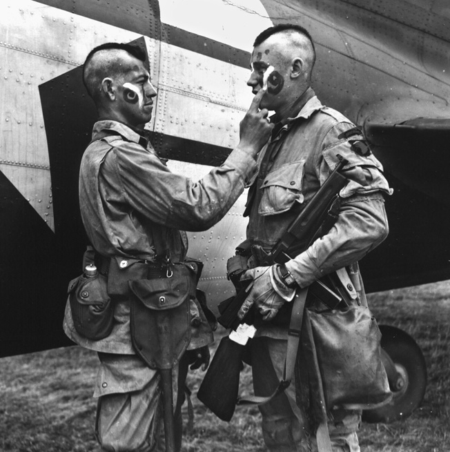 "Two members of the U.S. 101st Airborne Division, their hair shorn in Mohawk fashion, apply a little ""war paint"" prior to their jump into Normandy."