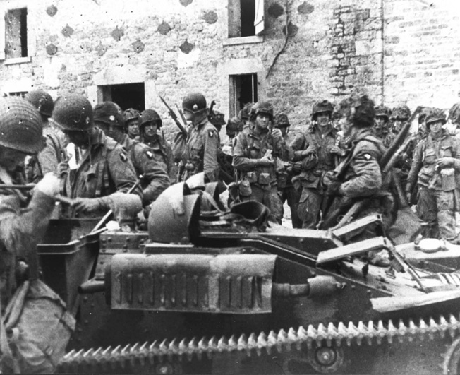 A group of 101st Airborne troopers congregate in the village of St. Marcouf before heading out on their next mission.