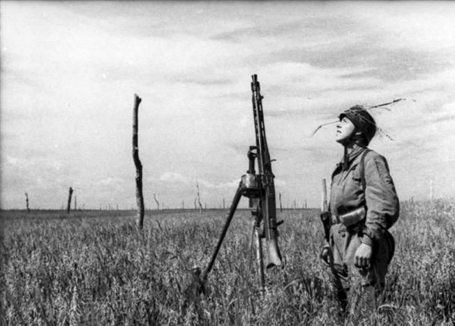 "A Fallschirmjäger looks skyward for any signs of the Allied invasion. Note the drum magazine on the MG 42 and the sturdy poles (Rommelspargel or ""Rommel's Asparagus"") planted in the open field to discourage enemy glider and parachute landings."