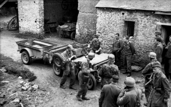 German troops gather around a captured American jeep and quarter-ton trailer. The Germans often used Allied weapons and vehicles whenever they could find them. Visible in the shadow of a French barn is a Porsche-designed Type 166 Schwimmwagen—the amphibious version of the Kübelwagen.