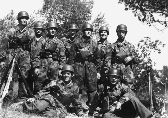 "A few members of FJR 6 pose for the cameraman. Note the splinter-camouflage jump smocks, leather cartridge pouches, ""stacked"" 98K rifles, and gas-mask bags on their chests. One man in the center is wearing the traditional Stahlhelm and not the Fallschirmjäger helmet."