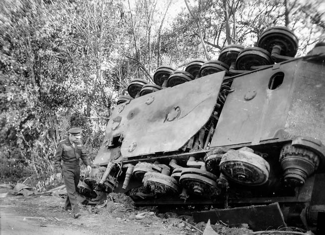 During his tour of the Falaise battlefield, Eisenhower inspects the remains of an overturned German tank near Chambois, southeast of Falaise.