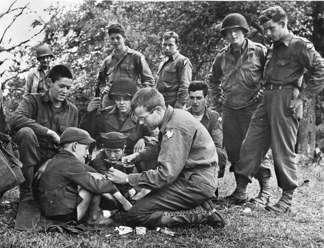 A private treats a small French boy's hand while other soldiers watch.