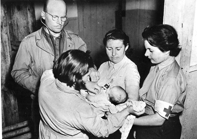 A truly Allied medical team tends to a French baby. The doctor is an American, the nurse in the center is a former Russian surgeon who was captured by the Germans in Leningrad, and the nurse on the right is a Swiss member of the French Army.