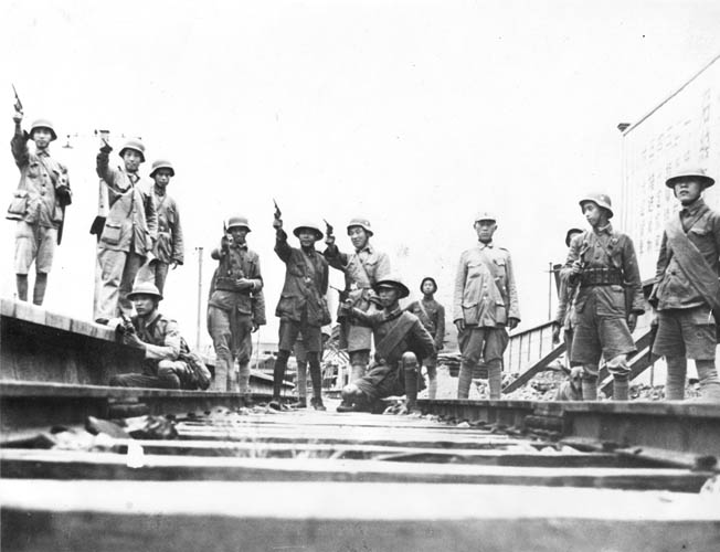Chinese troops strike heroic poses for a photographer during the Second Sino-Japanese War. Note that some of these Chinese soldiers are wearing the German coal scuttle-style helmet. German military advisers trained numerous units of the Nationalist Chinese Army.
