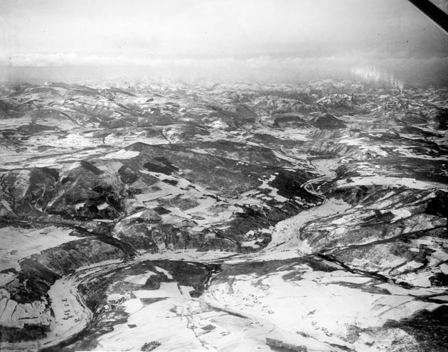 The rugged, unforgiving terrain of North Korea along the Chinese border is evident in this aerial shot taken shortly before the attack of the Chinese Communist Forces. The Chinese victory at the Chosin Reservoir came at a heavy cost in casualties from human wave attacks.