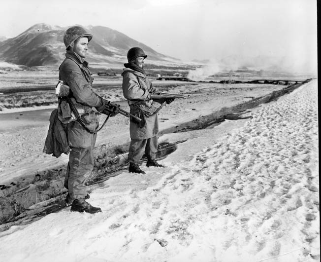 Two soldiers of the U.S. Army 7th Infantry Division patrol the banks of the Yalu River at the Chinese border.