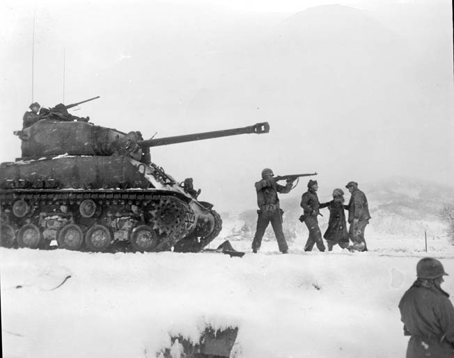 A tank of the Heavy Tank Company, 7th Infantry Division, engages the enemy at the Chosin Reservoir as infantrymen escort a prisoner to the rear.
