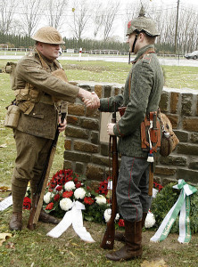Descendants of WWI veterans, dressed in period uniforms, symbolically shake hands in remembrance of the Christmas Truce.