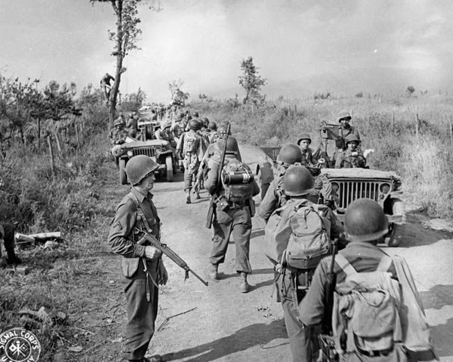 Initially held in reserve during the push for Cisterna, American soldiers of the 36th Infantry Division move toward the front lines. The 36th Division is well known for its heroic participation in the Italian Campaign, particularly the disastrous crossing of the Rapido River in January 1944.