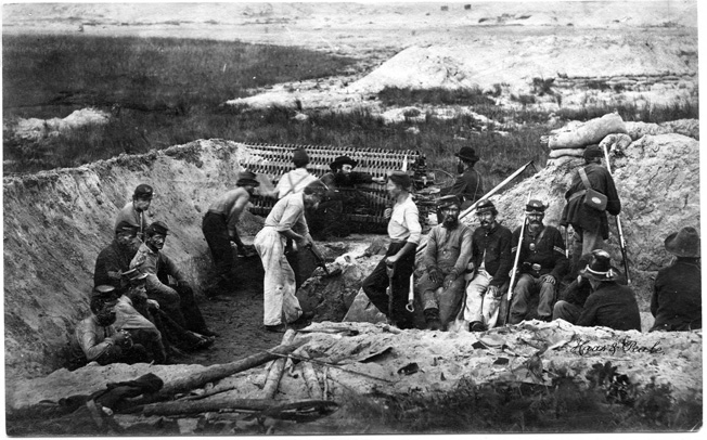 Union sappers at work on Morris Island, South Carolina, in 1863. The sap, a large basket containing logs, was used to protect the diggers and was rolled forward as a trench advanced. Armed infantrymen cover the workers as they dig.