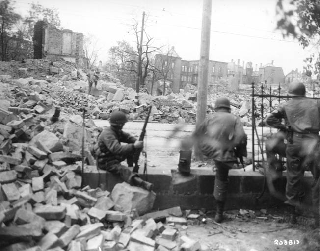 As Daly's men fought their way into the streets of the Bavarian city of Nuremberg, these troops of the U.S. 15th Infantry Regiment move forward warily on April 18, 1945. Nuremberg was considered the cradle of Nazism.