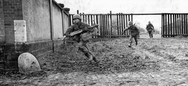 An American machine gunner sprints for cover while carrying his Browning .30-caliber machine gun as an ammunition carrier follows, his rifle slung across his back. This photo was taken in the French arrondissement of Sarreguemines at the height of the fighting in the Colmar Pocket during early February 1945.