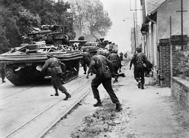 No. 4 Commando engages in house-to-house fighting with the Germans at Riva Bella, near Ouistreham. Sherman DD tanks of B Squadron, 13/18th Royal Hussars are providing fire support and cover.