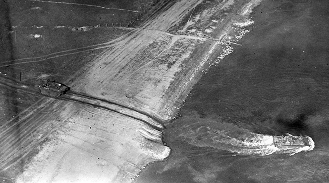 A British amphibious armored vehicle leaves the west bank of the Rhine, headed eastward. Another tank can be seen behind it on the bank. The photo was taken from a low-flying RAF plane on March 24, 1945.