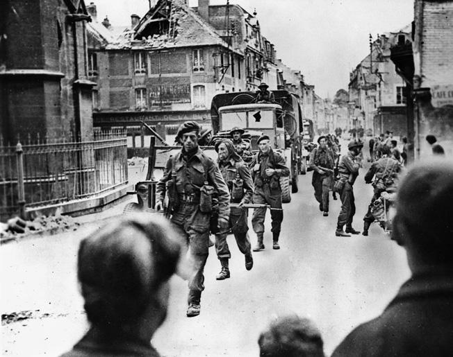 Men of No. 46 Commando, 4th Special Service Brigade, pass through the village of Douvres la Delivrande as French civilians look on, June 8, 1944.