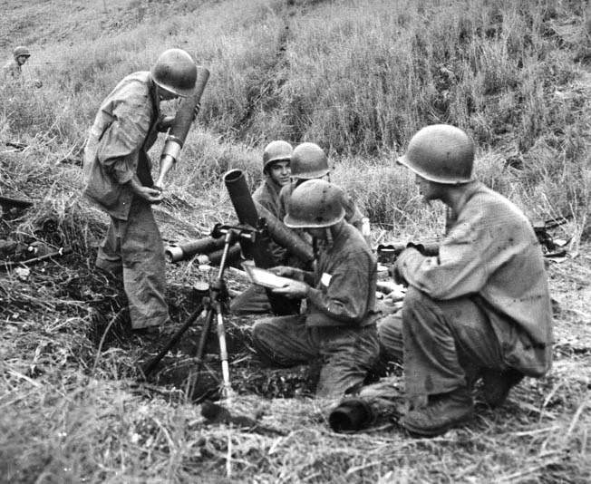 As its commander consults a map for firing coordinates, a Marine mortar team prepares to go into action against the Japanese. The 60mm and 81mm mortars of the Marines provided effective plunging fire against enemy infantry, and these were often the heaviest weapons available to the men of Company K during the heat of combat.