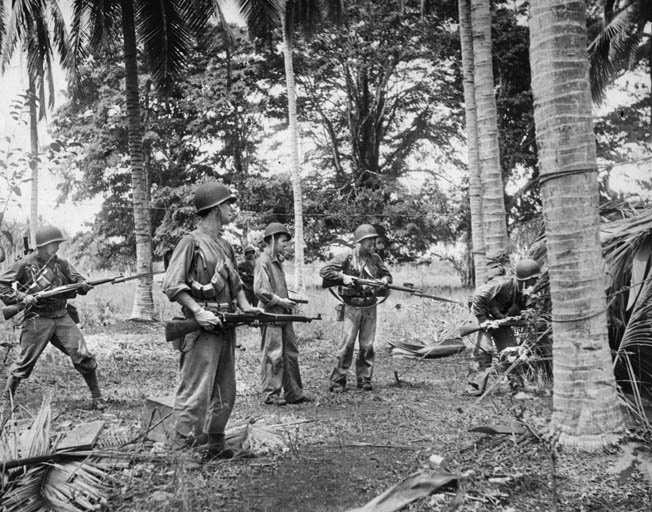 Posing for the photographer while on patrol in August 1942, these U.S. Marines were among the first to land on Guadalcanal. Three Marines are pictured armed with bolt-action Springfield Model 1903 rifles, two with the 16-inch-long, Model 1917 bayonets. The Marines' distinctive camouflage uniforms and semiautomatic M-1 Garand rifles were not issued in the Pacific until 1943.