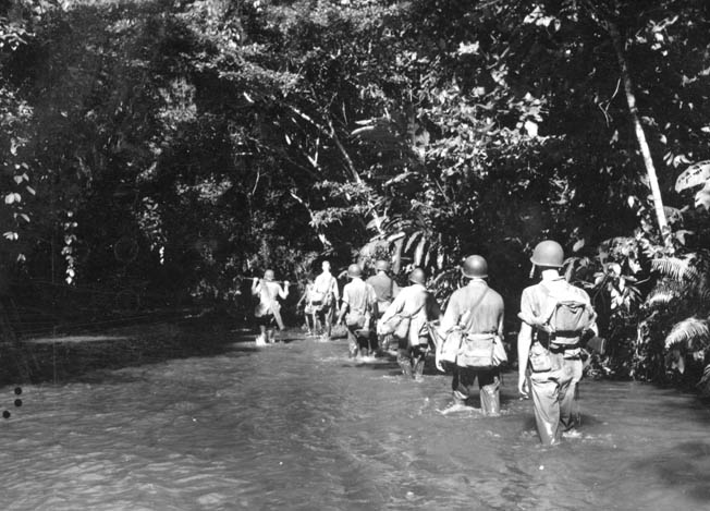Patrolling along the Tenaru River on Guadalcanal, U.S. Marines avoid the thick, nearly impassable jungle and find better footing along the shallow stream.