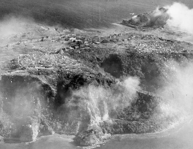 In this view of the plateau at Topside, American paratroopers are visible among the ruins of a headquarters building and barracks used by the Japanese. The golf course is shown at right, and several parachutes are seen at the edge of the jagged cliffs.