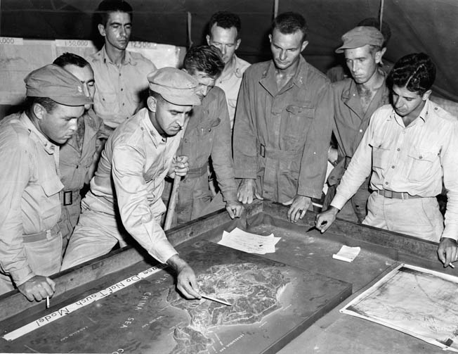 Colonel George Jones, commanding officer of the 503rd Parachute Regimental Combat Team, briefs staff officers and other personnel prior to the airborne assault on Corregidor. The troops faced stiff Japanese resistance after they landed.