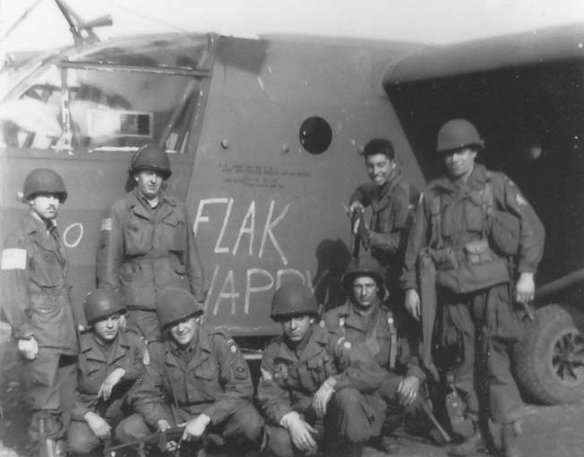 Members of the 319th Communications Section pose outside their glider, Flak Happy, on September 18. They are, left to right, kneeling: T-4 Ed Ryan, First Sergeant Irving Rosenwasser, George Barron, and Dimitrios Vassal. Standing, left to right: glider pilot Marks, Corporal Ernest Osborne, Seymour Englander, and Motor Pool Sergeant Jarret Fury.